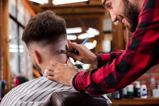 Парикмахер делает окончательные корректировки стрижки
