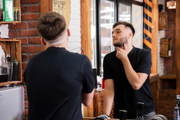 彼のひげをチェックする背面図の顧客