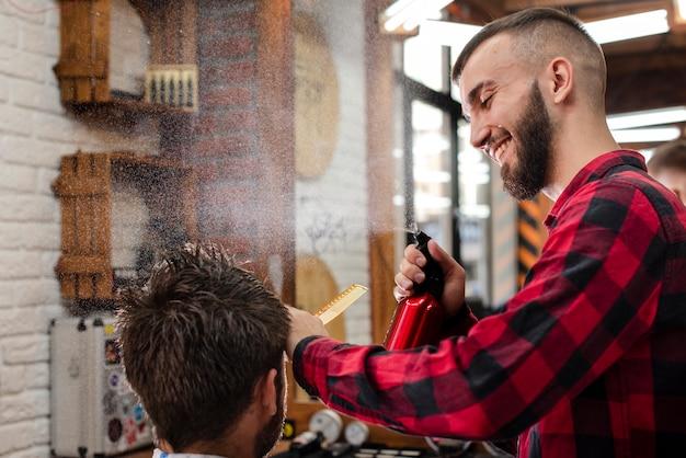 Счастливый парикмахер, распыляющий волосы клиента