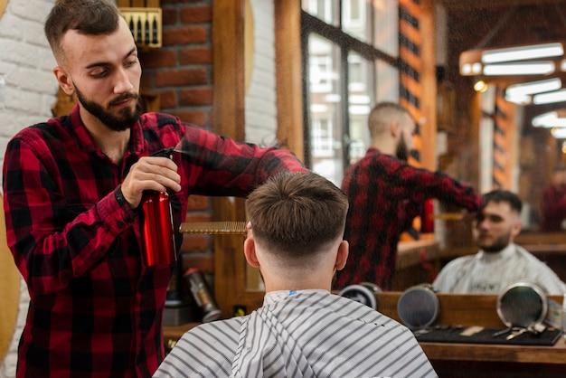 Парикмахер окропляет волосы молодого человека