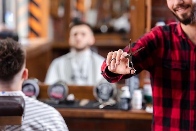 Парикмахер держит ножницы в правой руке