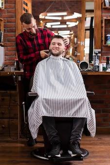 Молодой парикмахер и клиент улыбается