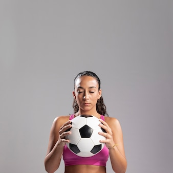 Подходящая женщина, держащая футбольный мяч