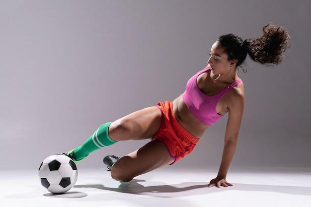 Подходит молодая женщина с футбольным мячом