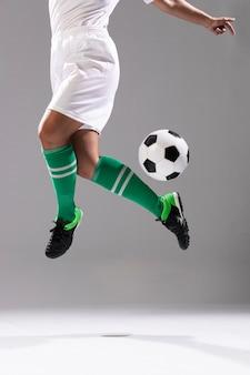 Взрослая женщина делает трюки с футбольным мячом