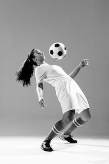 Полный выстрел подходит женщина с футбольным мячом