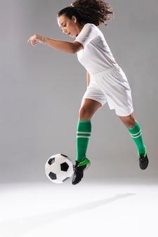 Подходящая молодая женщина играет в футбол