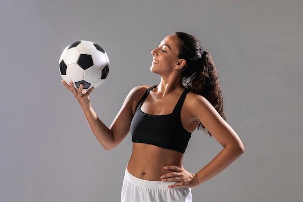 Вид спереди подходит женщина, держащая мяч