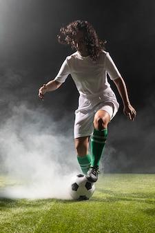 サッカーボールでフルショットの大人の女性