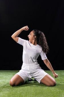 サッカーピッチの運動の若い女性