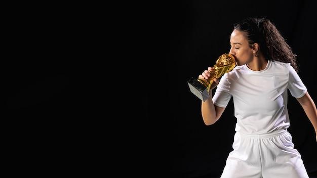 Подходит молодая женщина с футбольным трофеем