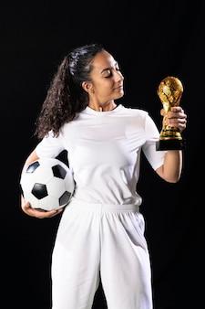 Подходит молодая женщина, держащая трофей и мяч