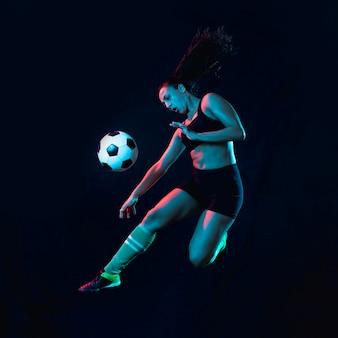 Подходящая молодая девушка пинает футбольный мяч
