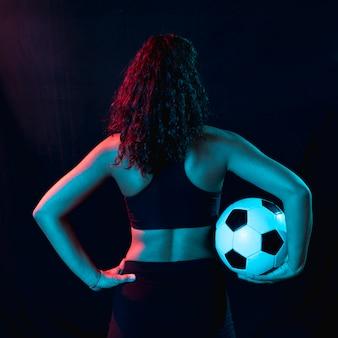 Вид сзади подходит молодая девушка с футбольным мячом