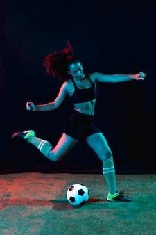 Спортивная молодая девушка пинает мяч