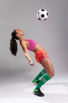 サッカーボールを持つ運動の若い女性
