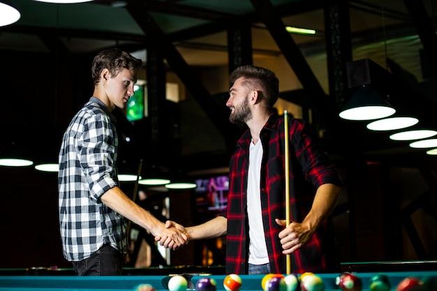 Средний выстрел парни пожимают руки возле бильярдного стола
