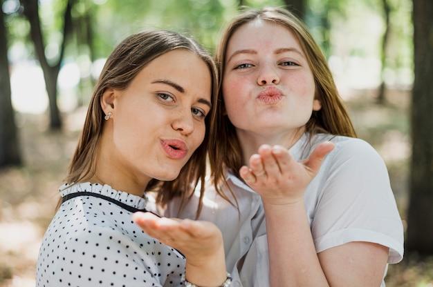 Две девочки-подростки дуют поцелуи