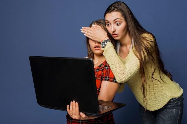 ミディアムショットのラップトップでショックを受けた女の子