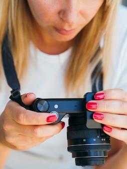 Женщина проверяет фотографии на камеру