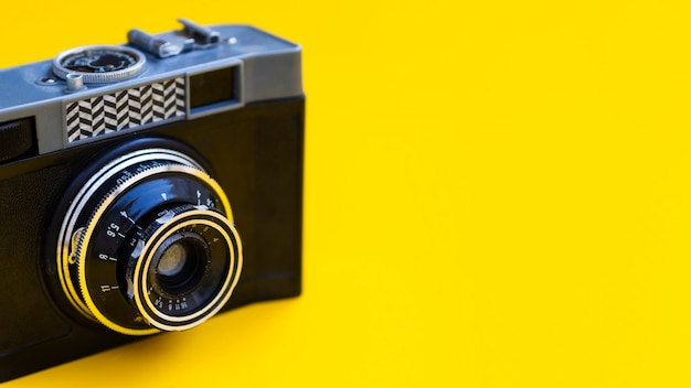 背景が黄色のビンテージ写真カメラのクローズアップ