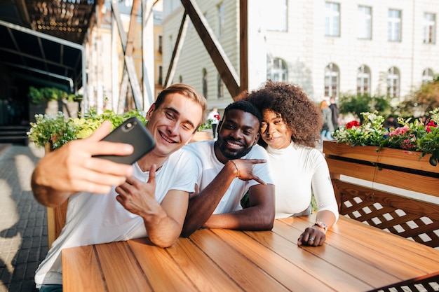 Межкультурные друзья в ресторане принимая селфи