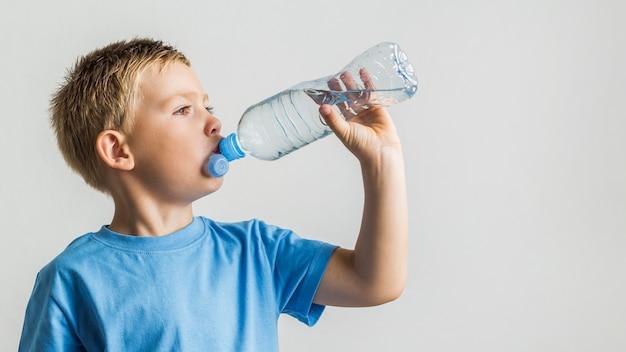 正面の若い男の子の飲料水