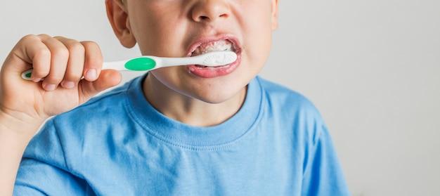 Крупным планом милый парень чистит зубы