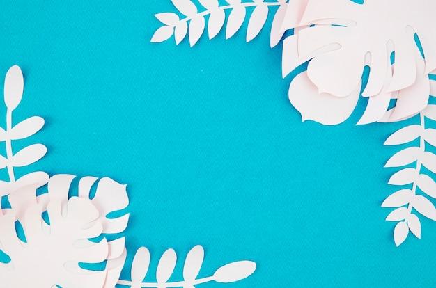 青色の背景に白いモンステラの葉