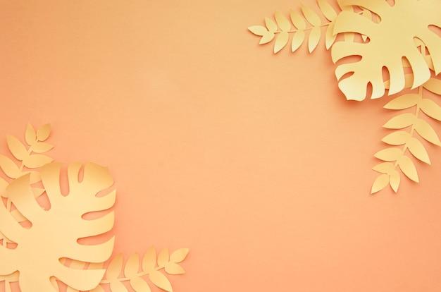 オレンジ色の背景にモンステラの葉コピースペース