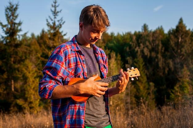 Мужчина играет на гавайской гитаре в лесу