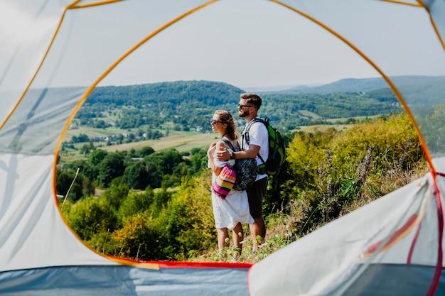 サイドビューカップル立って、テントからのショットを離れて見て