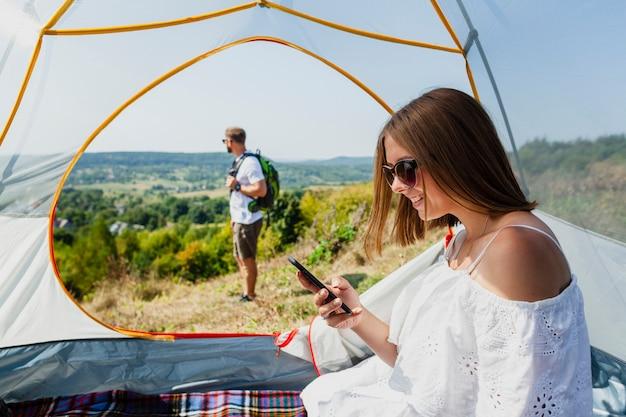Женщина в палатке смотрит на свой телефон