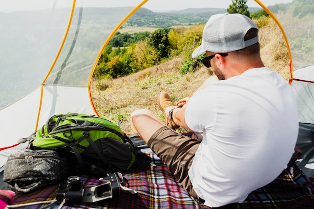 Мужчина в палатке надевает обувь