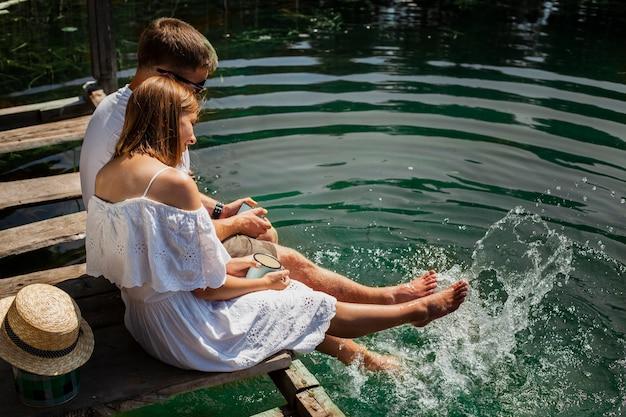 水で遊ぶカップルを抱き締めるの高ビューショット