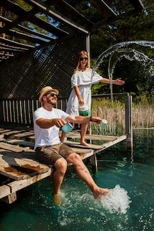 カップルの演奏と水に足で座っている男