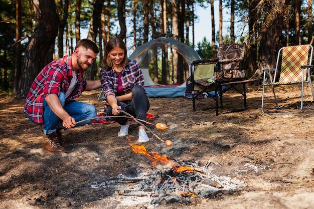 低角度のカップルのキャンプと料理