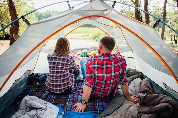 テントから自然の景色を楽しむ高角カップル