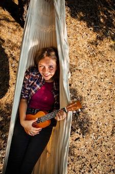 Высокий угол женщина играет на китаре