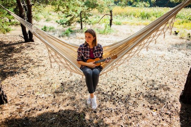 Женщина в гамаке с гитарой