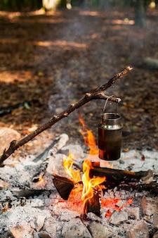 火の上の水で容器を保持している枝