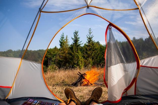 キャンプファイヤーを見てテントの男