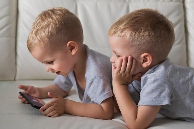 Маленькие братья крупным планом, играя на телефоне