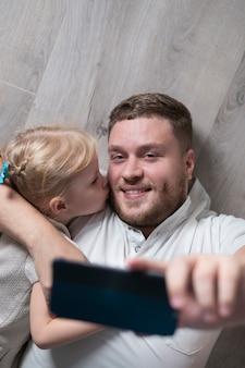 Маленькая девочка целует отца, принимая селфи