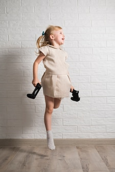 Возбужденная девушка с джойстиками в руках прыгает