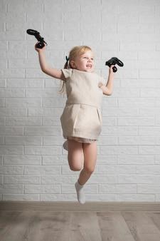 Улыбающаяся девушка с джойстиком в руке прыгает