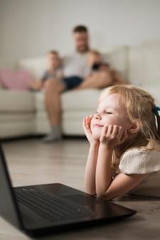 Маленькая девочка крупным планом глядя на ноутбук