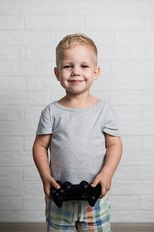 Маленький мальчик с джойстиком в руках у себя дома