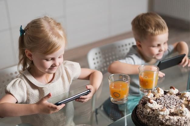 Братья и сестры дома играют на мобильном телефоне