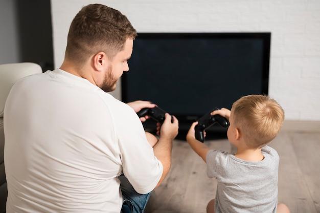 コントローラーのクローズアップで遊んでいる父と息子の背面図